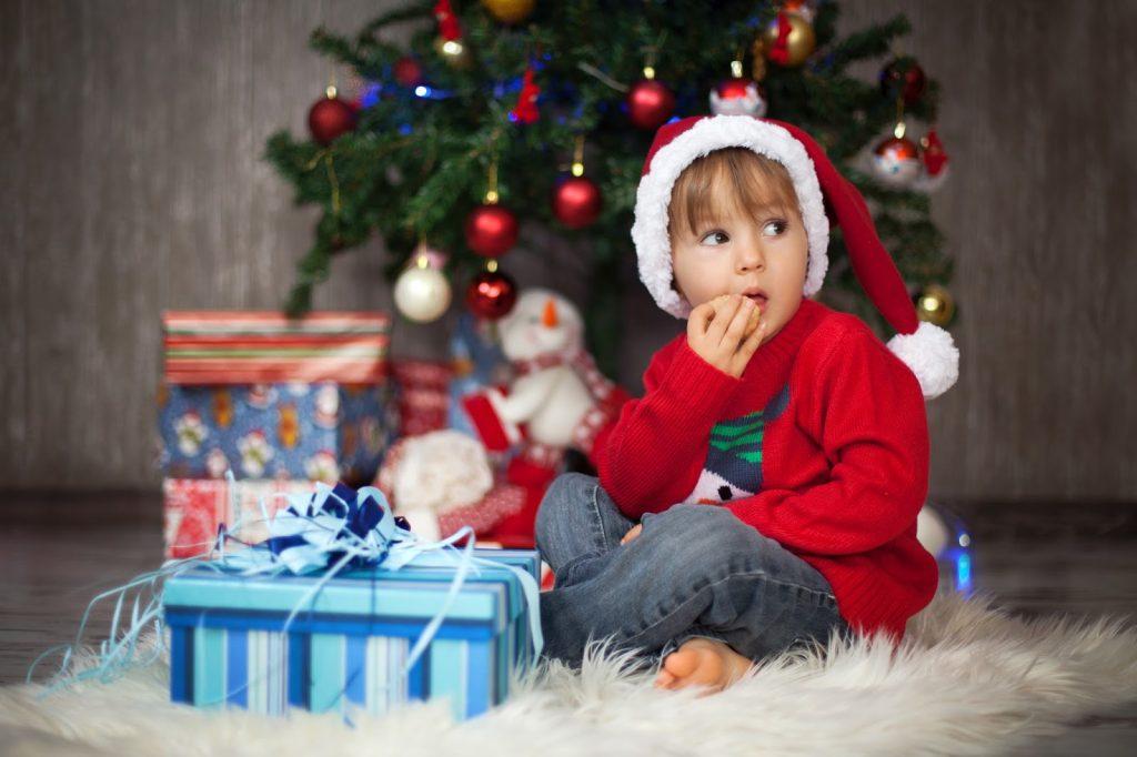 Boy sitting at christmass tree