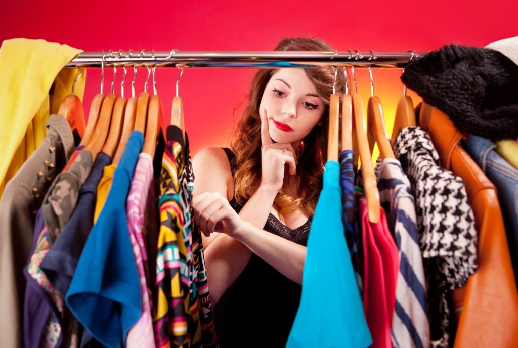 Girl checing out her clothes on a hanger.