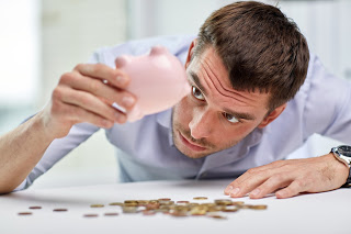 man shaking guinea pig bank to get coins