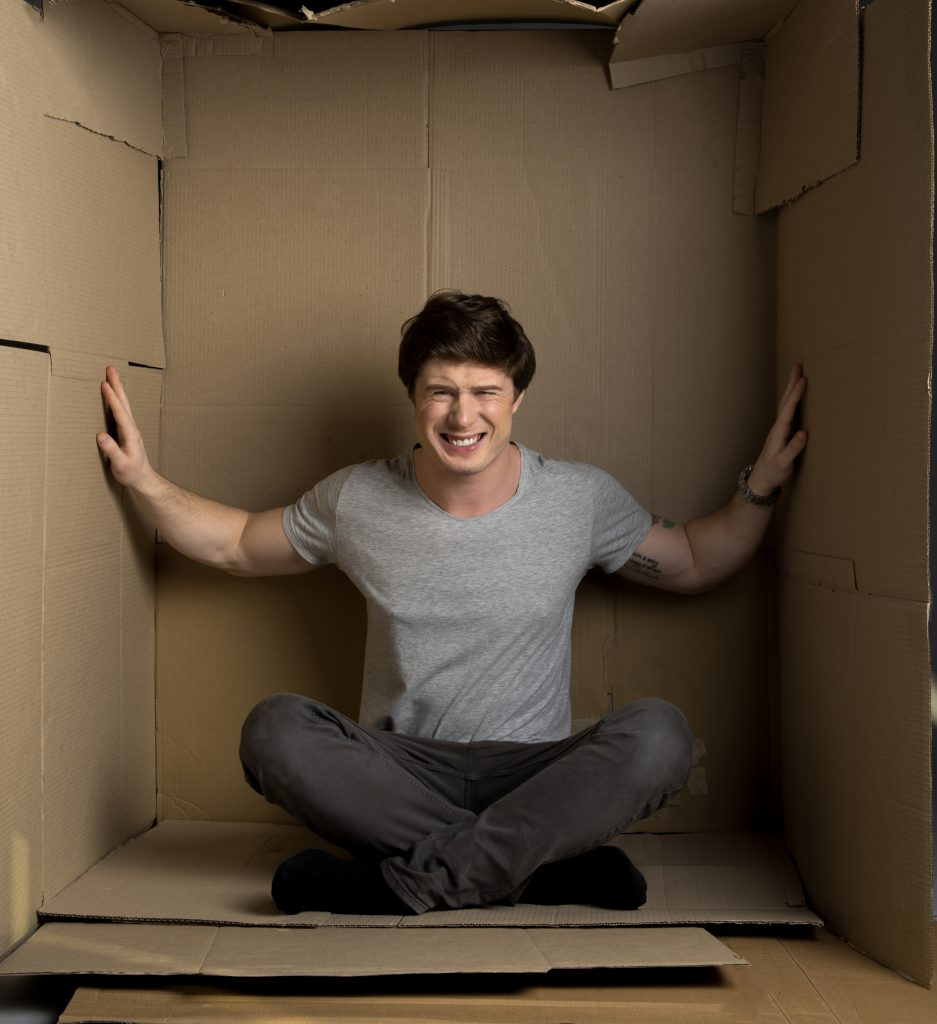 Guy is feeling discomfort in cramped room