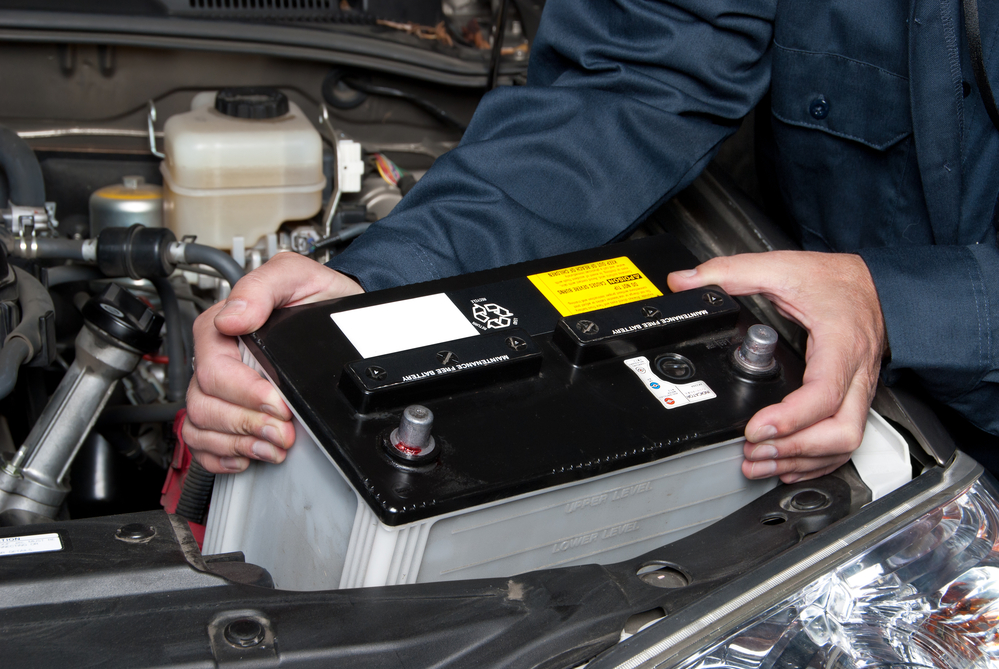 Classic car and car preparation for storage - A car mechanic replaces a battery.