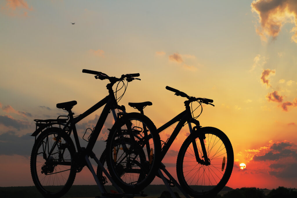 Summer Family Bike Self Storage Solutions - Bikes on top of a car against a beautiful sunset.